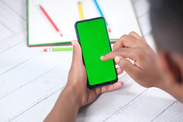 Вид сзади молодого человека, использующего смартфон на столе