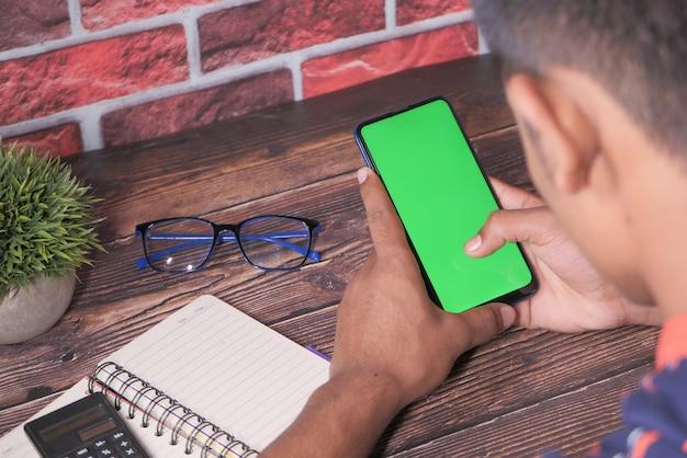 Вид сзади молодого человека с помощью смартфона