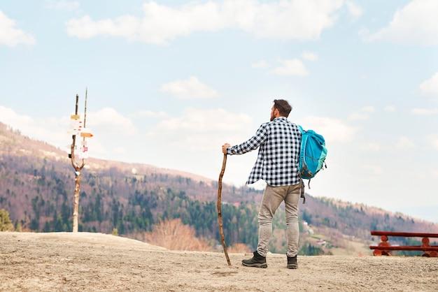 旅行中のバックパックを持つ若い男の背面図