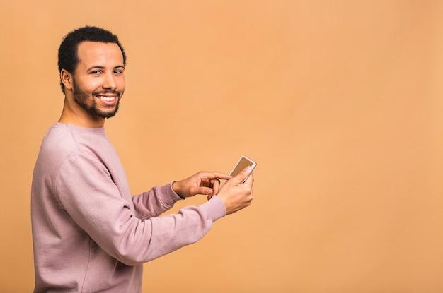 ベージュの上に孤立して立っている間デジタルタブレットに取り組んでいる若い男の背面図。