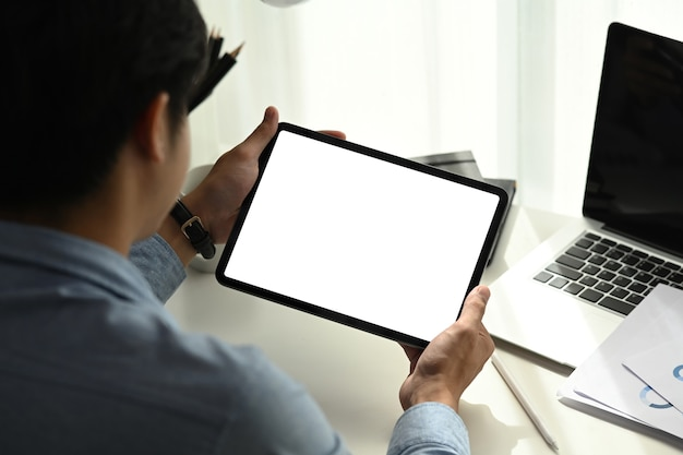 태블릿 휴대용 전자 장치에서 작업하고 인터넷에서 정보 문서를 찾는 젊은 남자의 후면보기.