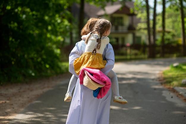 Вид сзади молодой матери, прогулки с маленькой дочкой в красивом летнем парке