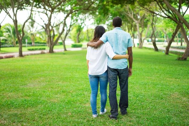 포용과 공원에서 산책 젊은 다민족 부부의 후면보기.