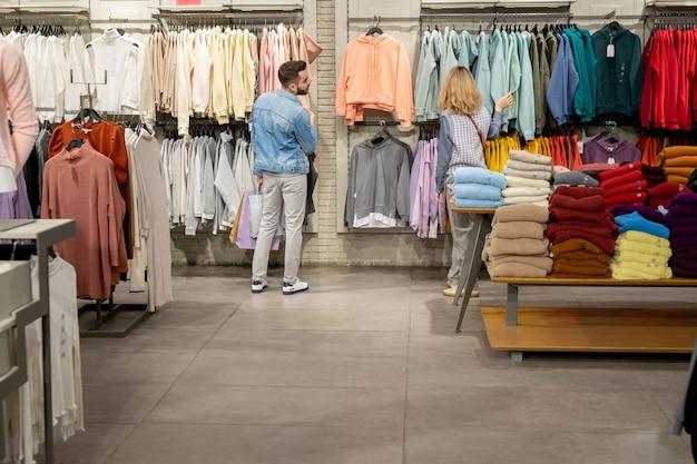 モール内の衣料品店で新しい服を選ぶ若者の背面図
