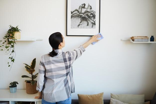 그녀는 그림에서 걸레로 먼지를 닦아 방에서 집안일을하는 젊은 여자의 후면보기