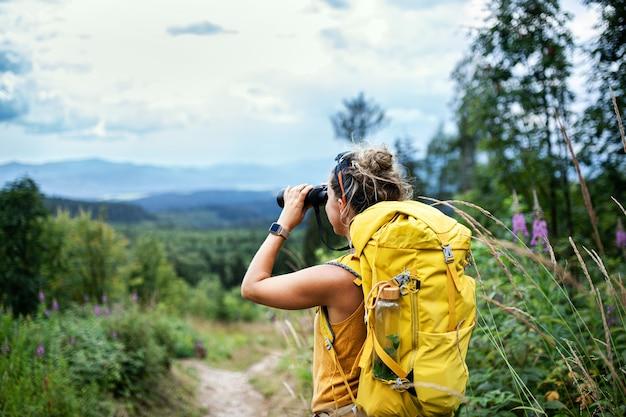 쌍안경을 사용하여 자연에서 하이킹 여행을 하는 젊은 여성 등산객의 뒷모습.