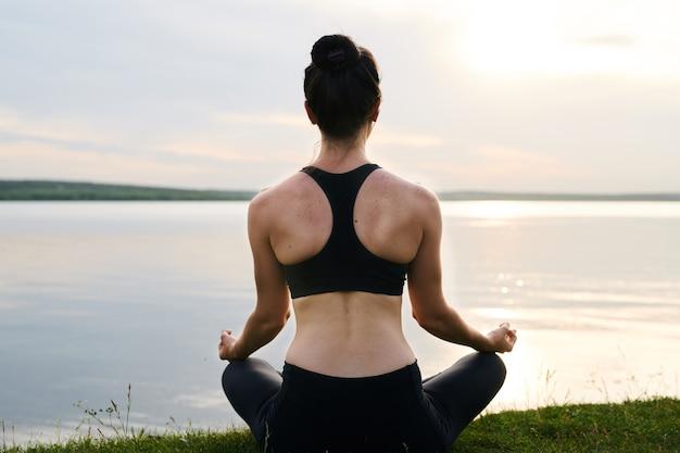 草の上に組んだ足で座っていると日没で瞑想の黒いスポーツウェアの若い女性の後姿