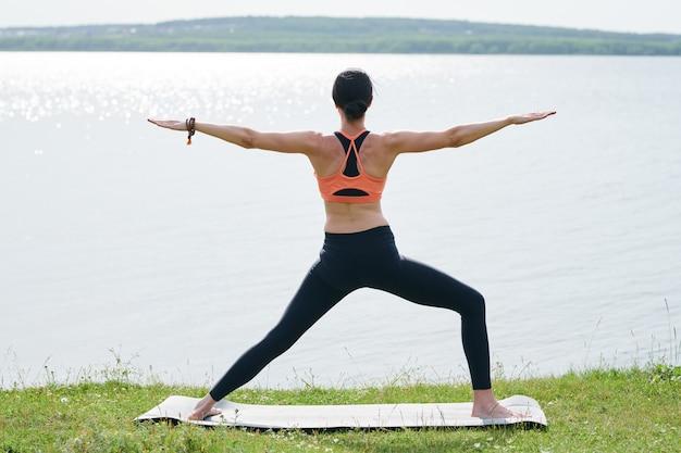 ヨガのマットの上に立って、湖を熟考しながら腕の平行な地面を上げるレギンスで若い女性の後姿