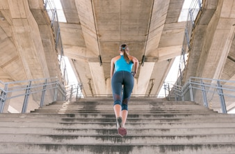 Rear view of young woman in sports clothing jogging on staircase