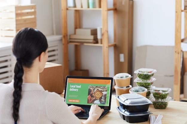 Вид сзади молодой женщины, сидящей за столом с коробками с едой и заказывающей еду онлайн в офисе