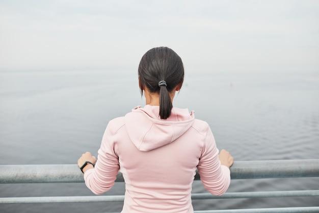 橋の上に立って美しい海の景色を見ている若い女性の背面図