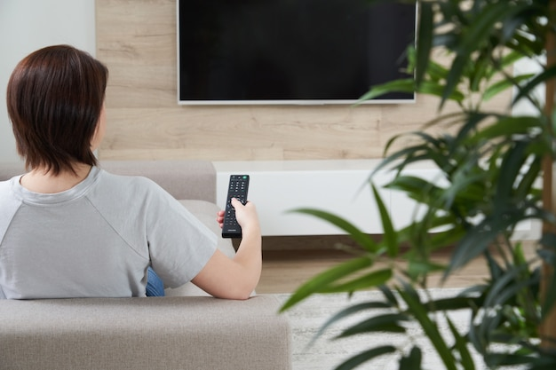 소파에 앉아있는 동안 텔레비전을보고 리모컨을 들고 젊은 여자의 후면보기