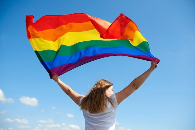 Вид сзади молодой женщины, размахивающей радужным флагом Бесплатные Фотографии