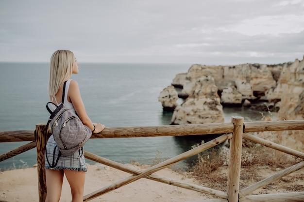 背景のビーチの海の景色の地平線上のバックパック旅行者と若い女性の背面図。
