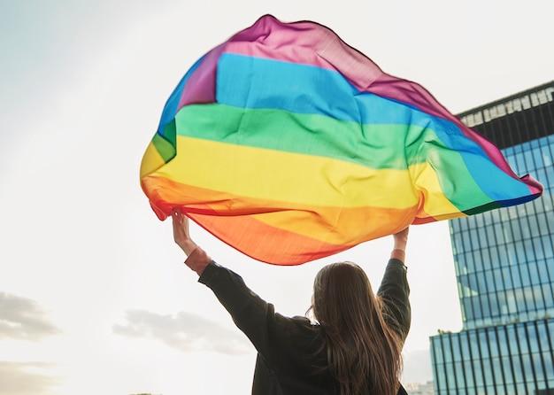 Вид сзади молодой женщины с радужным флагом