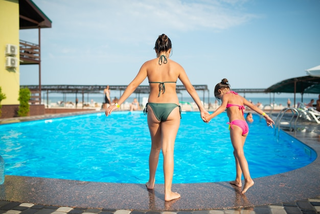 Rear view older sister holds hand of younger sister before jumping into clear blue warm water in the pool while relaxing at sea during summer holidays. long-awaited travel concept.