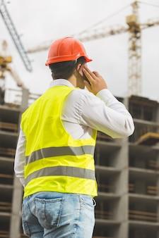 電話で話し、建築現場を見ている建設エンジニアの背面図