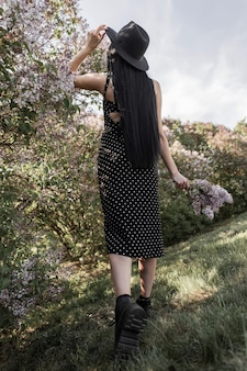 Вид сзади на элегантную брюнетку с шикарными длинными волосами в стильной шляпе в модном черном женственном платье в кожаных туфлях с сиреневыми цветами возле цветущих деревьев в парке на закате. девушка любит май.