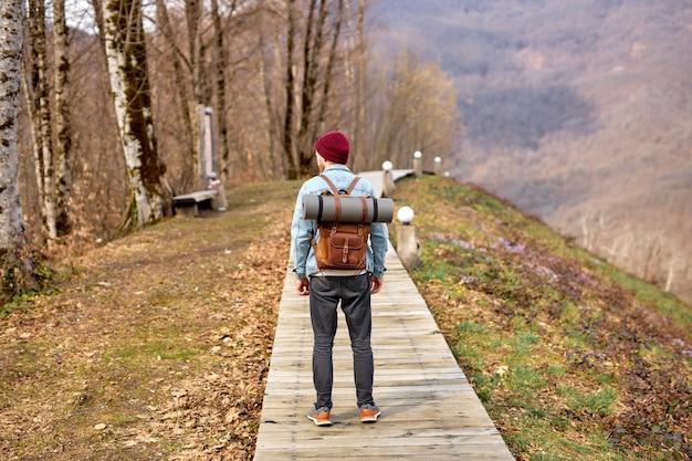 山を探索するマンハイカーの背面図、旅行健康的なライフスタイルの冒険旅行