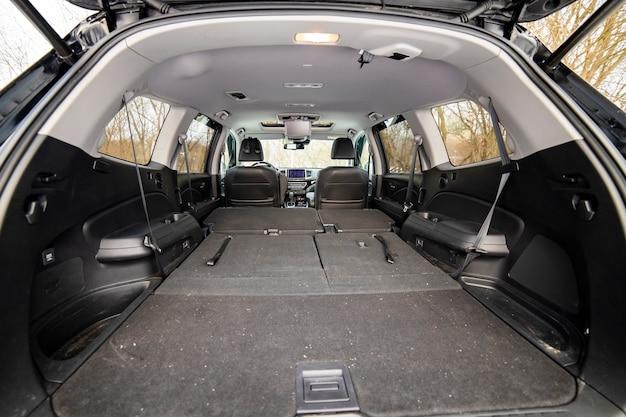 접힌 조수석이 있는 후면 보기 개방형 자동차 트렁크. 큰 빈 플랫 플로어 자동차 트렁크를 닫습니다. 거대한 suv 트렁크