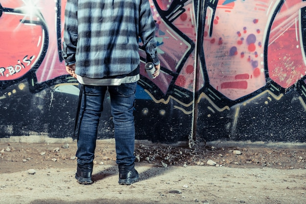 Rear view of person standing in front of graffiti wall holding spray bottle