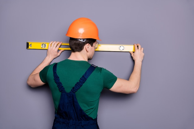 Rear behind view photo of handsome masculine worker guy skilled engineer measure rack length of wall wear t-shirt safety dungarees protective helmet glasses isolated grey wall