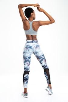 Портрет вид сзади афро-американской женщины, показывающей ее бицепс, изолированные на фоне