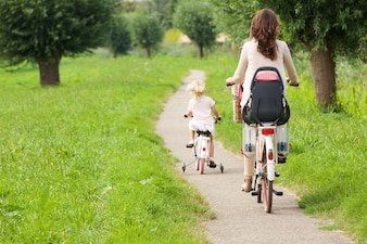 Rear view portrait of mother and daughter riding bicycles in park