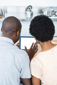 Rear view of pregnant couple looking at digital tablet in kitchen