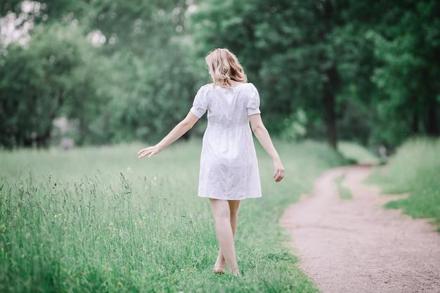 草の上を裸足で歩く妊婦の背面図