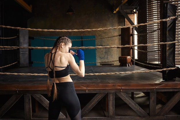 Rear view of professional female boxer with two braids standing in empty gym with boxing ring in background, training alone,