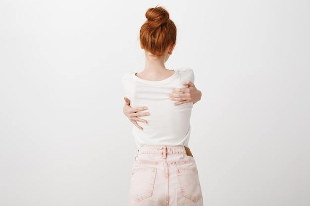 Rear view of redhead girl hugging herself