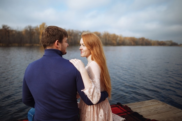 Rear view of romantic young couple sitting on pier enjoying amazing view