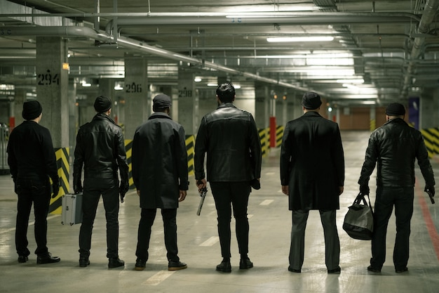 Rear view of row of criminals or gangsters in black standing on parking area while waiting for man with buyout