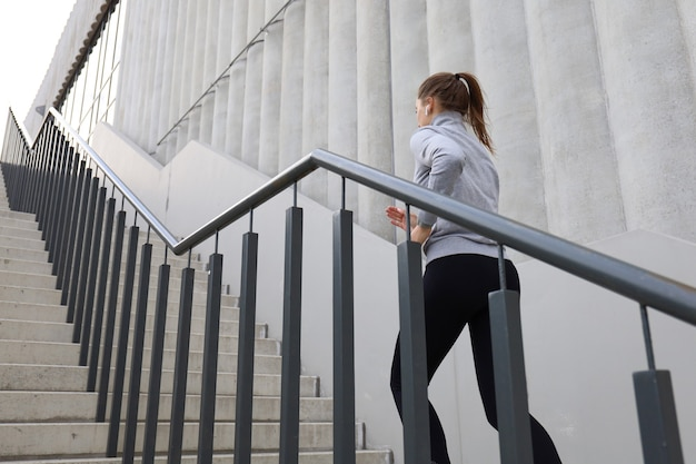 Rear view of runner athlete running on stairs. woman fitness is jogging oudoors.