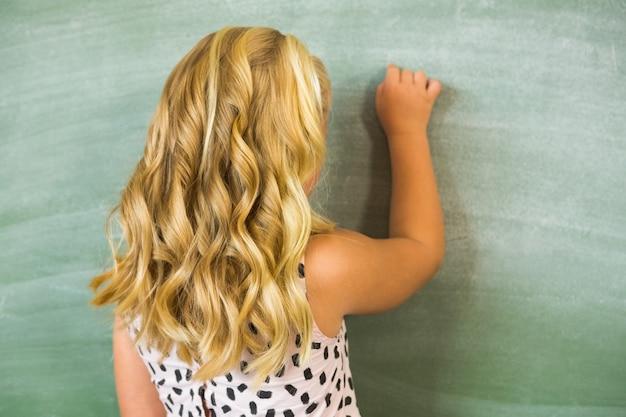 Rear view of school girl writing on chalkboard in classroom