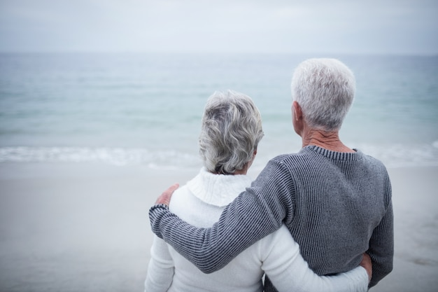 Rear view of senior couple embracing on beach