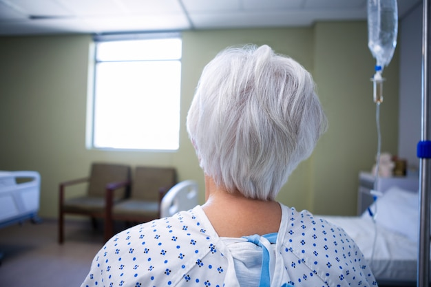 Rear-view of senior patient sitting in ward