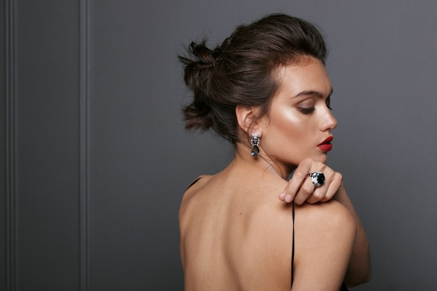Rear view of a sexy brunette woman in black dress with bare shoulders, wears blue stone earrings and rings over grey dark background.