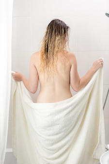 Rear view of sexy woman wiping with towel after bath