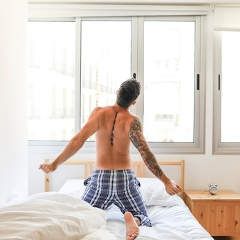Rear view of a shirtless man stretching on bed
