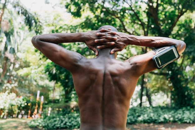 Rear view of a shirtless young man with his hands behind head stretching in the park