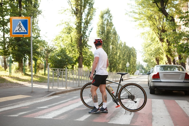 Rear view shot of a male cyclist crossing road with his bicycle on crosswalk, copy space