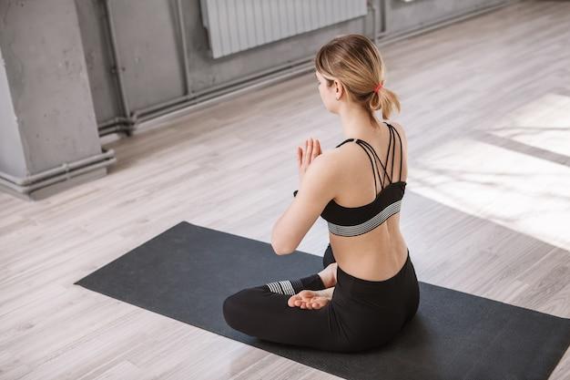 ヨガの練習の後に瞑想するスポーツウーマンの背面ショット