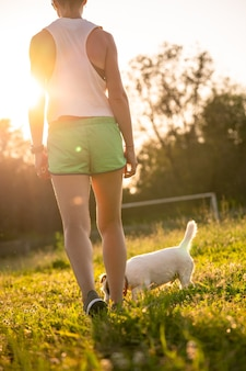 Выстрел вид сзади подходящей женщины в спортивной одежде, идущей по спортивному полю. фитнес-тренировка на закате.