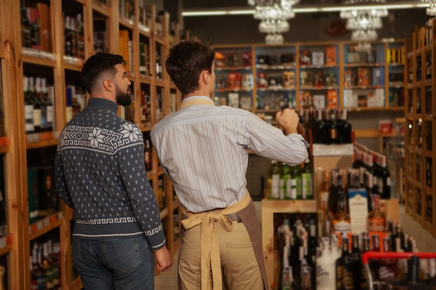 Rear view shot of a professional sommelier helping his male customer choosing wine to buy, copy space. salesman and client at the supermarket