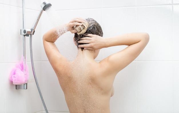 Rear view shot of sexy woman washing hair