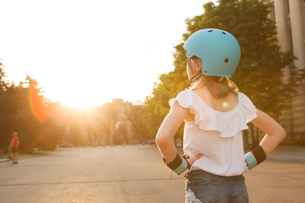 Rear view shot of young rollerblader girl wearing helmet, looking away on sunset in the city, copy space