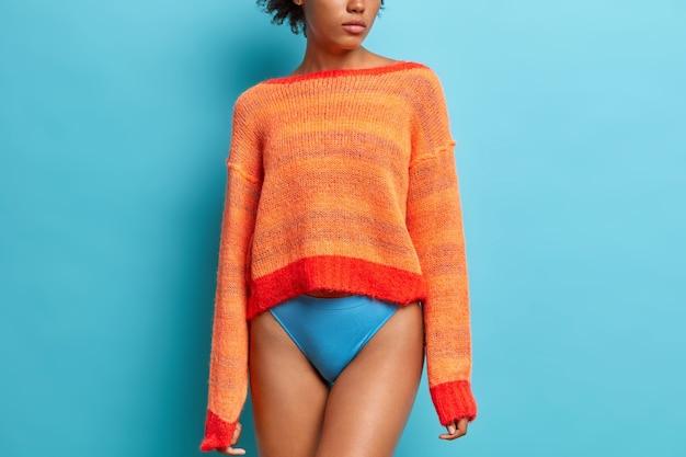 Rear view of slim woman wears long sleeved orange jumper and panties has long legs fit smooth skin fit figure models against blue studio wall