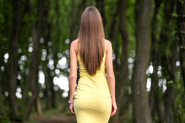 Rear view of a slim woman in yellow dress standing alone in moody dark forest.